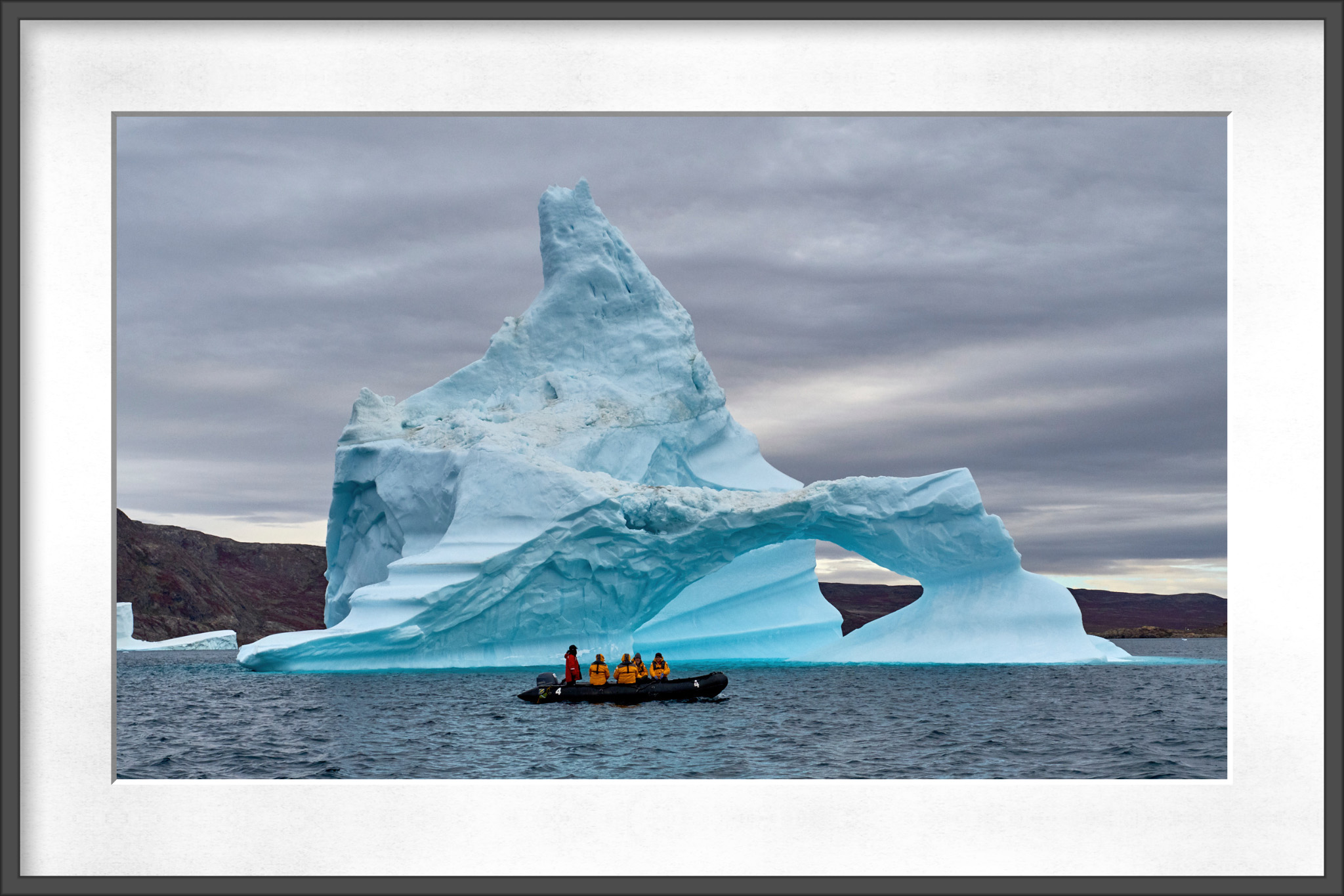 One of our Zodiacs cruising by a large iceberg